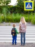 Le garçon et la fille veulent traverser la route à un passage pour piétons images libres de droits