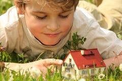 Le garçon et la maison modèlent dans l'herbe Photo stock