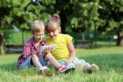 Le garçon et la petite fille jouent avec le comprimé en parc Photos stock