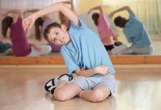 Le garçon et le groupe se sont engagés dans la formation physique photo libre de droits