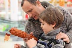 Le garçon et le père choisissent la saucisse dans le système Photographie stock