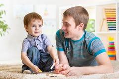 Le garçon et le père d'enfant jouent avec le jouet de puzzle Photos libres de droits