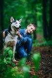 Le garçon et le sien poursuivent le chien de traîneau sur le fond des feuilles au printemps Images libres de droits