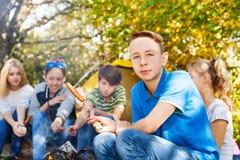 Le garçon et les ados s'asseyent sur le terrain de camping avec des saucisses Photo stock