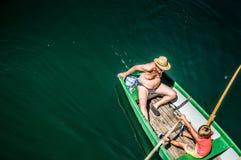 Le garçon et le papa montent un bateau sur le lac Photographie stock libre de droits