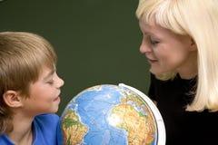 Le garçon et sa mère regardent le globe Images stock