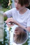 Le garçon et sa réflexion dans le miroir apprêtent Photos stock
