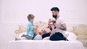 Le garçon et ses parents se situent dans le lit et jouent avec les jouets mous Le concept d'une famille heureuse La famille heure clips vidéos