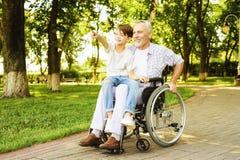 Le garçon et son grand-père marchent en parc Le vieil homme s'assied sur un fauteuil roulant Photographie stock libre de droits