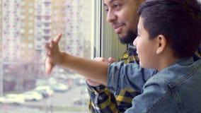 Le garçon et son père ondulent la fenêtre banque de vidéos