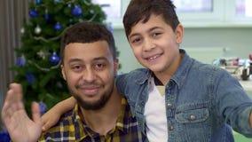 Le garçon et son père ondulent leurs mains banque de vidéos