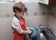 Le garçon européen lave des plats à la maison image stock