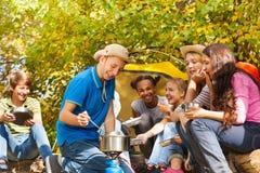 Le garçon fait cuire la soupe dans le pot pour des amis au terrain de camping Photo stock