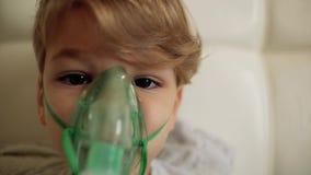 Le garçon fait l'inhalation tout en se reposant sur le lit l'enfant inhale la vapeur banque de vidéos