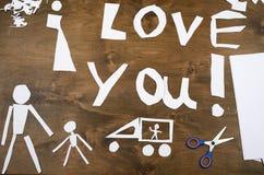 Le garçon fait l'origami - voiture et famille, enfants, parent, je t'aime le texte, vue supérieure sur le fond en bois Photo libre de droits