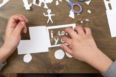 Le garçon fait l'origami - voiture et famille, enfants, parent, je t'aime le texte, vue supérieure sur le fond en bois Photos stock