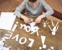 Le garçon fait l'origami - voiture et famille, enfants, parent, je t'aime le texte, vue supérieure sur le fond en bois Photos libres de droits