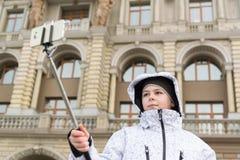 Le garçon fait le selfie au téléphone avec le bâton de selfie sur le fond des vues Images libres de droits