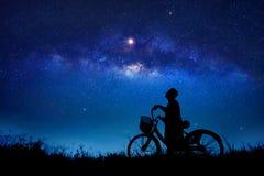 Le garçon fait un cycle au beau milieu de la galaxie d'étoiles image stock
