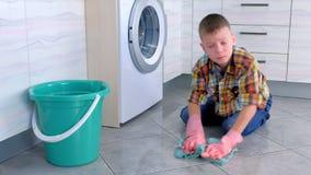 Le garçon fatigué dans les gants en caoutchouc lave le plancher dans la cuisine regardant la caméra Les fonctions ? la maison de  banque de vidéos