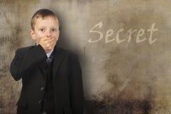 Le garçon a fermé sa bouche avec sa main et garde un secret Image stock