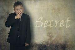 Le garçon a fermé sa bouche avec sa main et garde un secret Image libre de droits