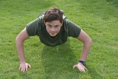 Le garçon forme des pousées dehors dans le jardin image stock