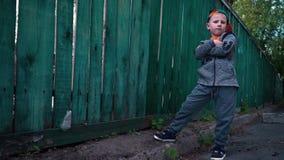 Le garçon frais change des expressions du visage, enfant posant sur l'appareil-photo près de vieil en bois clips vidéos