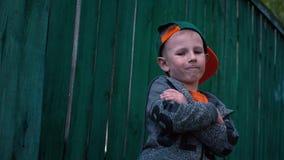 Le garçon frais change des expressions du visage, enfant posant sur l'appareil-photo près de vieil en bois banque de vidéos
