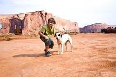 Le garçon frotte un chien dans le paysage de la vallée de monument Photographie stock libre de droits