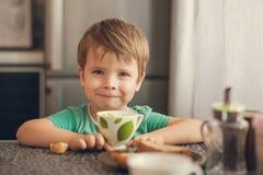 Le garçon gai boit du lait, mange du pain grillé pour le petit déjeuner Image stock