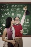 Le garçon gai gagne le baiser de trophée de maths par la mère Image libre de droits