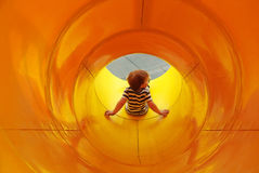 Le garçon glisse vers le bas dans le tube Images stock