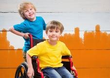 Le garçon handicapé dans le fauteuil roulant avec l'ami avec l'orange lumineuse a peint le fond Photos stock