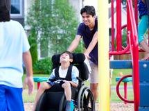 Le garçon handicapé dans le fauteuil roulant appréciant observant des amis jouent au pair Image libre de droits