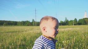 Le garçon heureux allant avec une fleur blanche de pissenlit dans le sien main près de la ligne électrique banque de vidéos