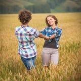 Le garçon heureux et la fille de l'adolescence marchant dans un seigle mettent en place Photographie stock