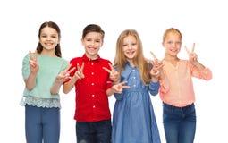 Le garçon heureux et les filles montrant la main de paix signent Photo stock