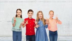 Le garçon heureux et les filles montrant la main de paix signent Photos libres de droits