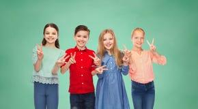 Le garçon heureux et les filles montrant la main de paix signent Image libre de droits
