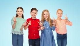 Le garçon heureux et les filles montrant la main de paix signent Images libres de droits