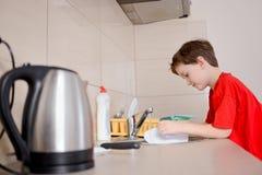 Le garçon heureux et souriant de 7 ans lave des plats Photographie stock