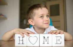 Le garçon heureux joue avec des cubes et le remonte dans le mot Photo libre de droits