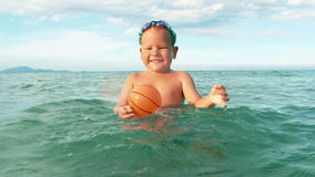 Le garçon heureux joue avec la boule dans le mouvement lent de mer banque de vidéos