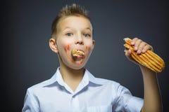 Le garçon heureux mangeant le grand sandwiche ou hot dog a isolé le fond gris Photographie stock libre de droits