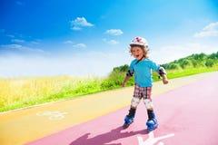 Le garçon heureux se précipitant en descendant sur fait du roller Photos libres de droits