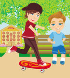 Le garçon heureux sur une planche à roulettes Photo stock