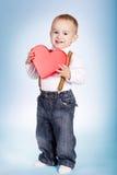 Le garçon heureux tient le coeur dans des mains Images stock