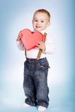 Le garçon heureux tient le coeur dans des mains Photo stock