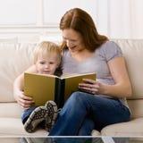 le garçon il mère de écoute a affiché l'histoire aux jeunes Photo stock